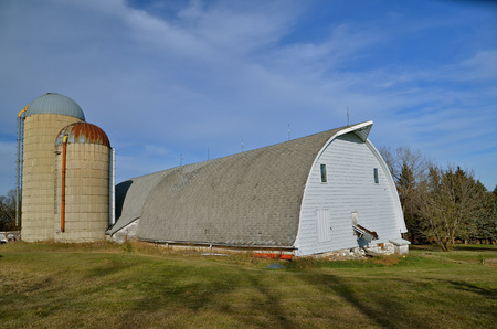 A n old white around topped barn with several silos and a barn cleaner
