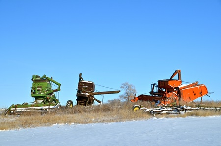 combines: Three old self propelled combines left in a snow covered grass field
