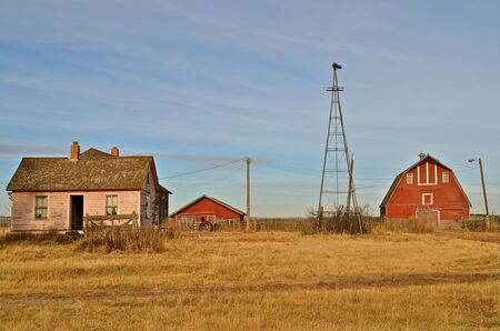 barn barnyard: Old rural homestead of house, barn, pig shed, and weather vane Stock Photo