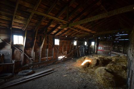 Decaying interior of an old barn as sun streams through the open windows