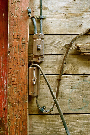 antiquated: Antiquated electrical wiring in an old barn with carvings on the door frame, Stock Photo