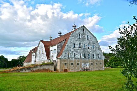 cupolas: Large majestic white barn with many windows and cupolas