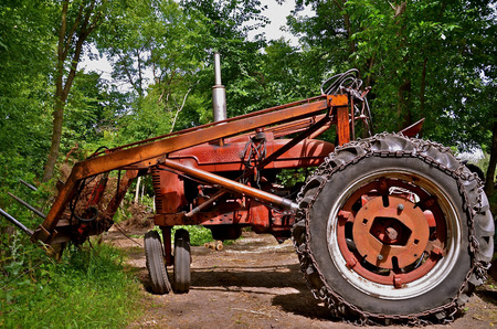 perpendicular: An old red tractor with a front end loader is parked in a driveway with the front wheels cranked perpendicular.