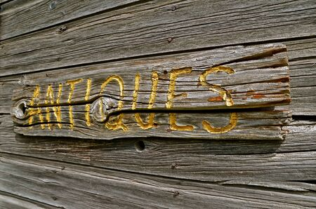 routed: On the siding of an old building is a weathered wood sign indicating ANTIQUES