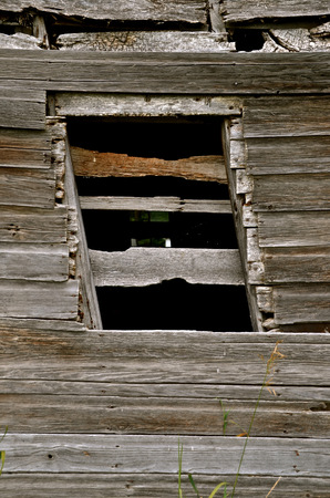 lopsided: A sagging barn composed of weathered wood results in a lopsided window frame.