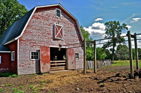 barn barnyard: Back of the red hip roofed barn where a track for a manure carrier is still intact.