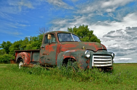 Old pickup in long grass displaying much patina Stock Photo