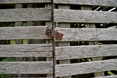 hasp: Rusty hasp keeps doors of a weathered wood corn crib closed