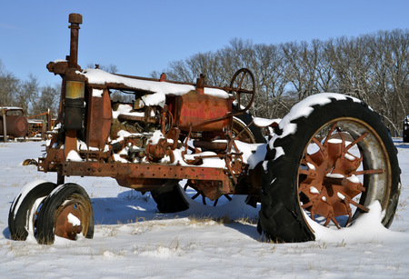 Snow covers an old rusty tractor after a snow storm