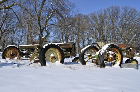 old tractors: Old tractors lined in a row are covered with snow