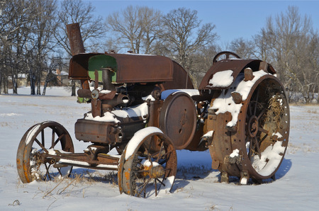 Old retired tractor missing parts resting in the snow photo