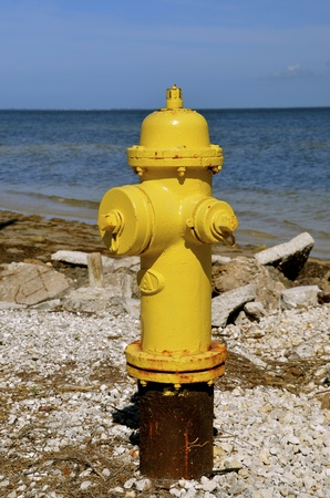 Yellow fire hydrant located on the shoreline of the ocean Stock Photo
