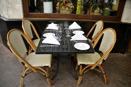 formal place setting: A formal outdoor eatery with a formal place setting and chairs for dining