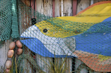 fish net: Artsy wood fish on old wood siding decorated with a fish net and mini bobbers