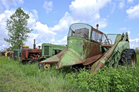 junked: Row of old junked tractors includes a mounted two row corn picker Stock Photo
