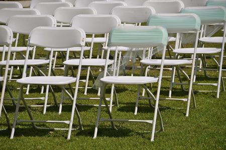 外の結婚式のための芝生の上の椅子を並べ、