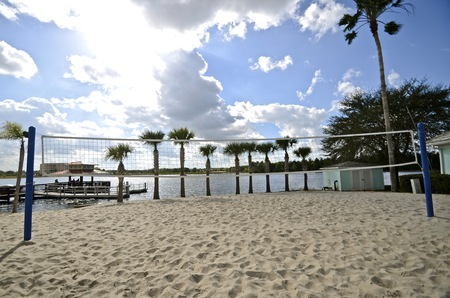 palm lined: A volleyball court, net, and standards are located next to a beach lined with palm trees shows extensive usage. Stock Photo
