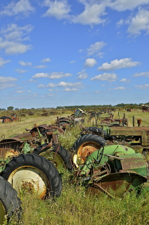 junked: Rows of green junked tractors and machinery up in a salvage and junkyard Stock Photo