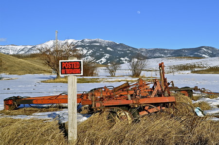 trespassing: No trespassing sign on a field withe some old machinery standing idle.