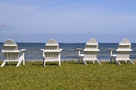 front facing: Lawn chairs on the grassy beach facing the ocean front Stock Photo