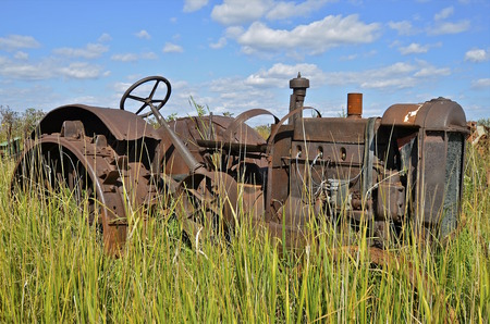 lugs: Rusty old tractor with steel wheels and lugs in the long grass