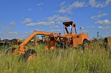 leveler: Huge orange road grade is parked in a salvage and junkyard Stock Photo