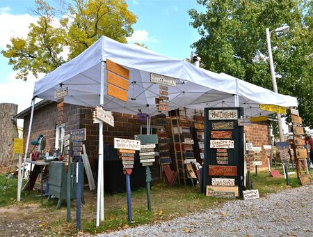 Craft booth with carved signs from a router displayed under a canopy