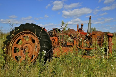 junkyard: Old tractor parked in a junkyard full of weeds and long grass Stock Photo