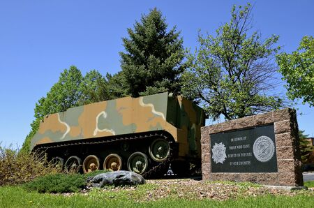 honoring: Armored Personnel Carrier displayed by a monument honoring the soldier of the USA