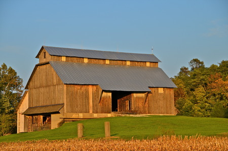 amish: Beautiful Amish barn with weathered wood located on the crest of a hill