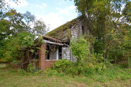 Old dilapidated house falling into ruins is surrounded by bushes and trees. Imagens