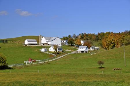 Krásný statek s bílou budovy v Amish zemi se začátkem podzimní zbarvení.