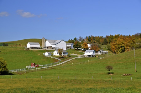 Beautiful farm with white building in Amish country with the beginning of the autumn coloring.