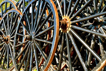 Black Amish buggy wheels leaning against a fence