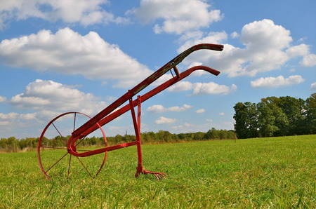 cultivator: Antique one wheeled field cultivator stands unassisted in a wide open field Stock Photo