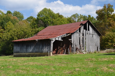 Weathered rickety barn with a leanto is in need of repair