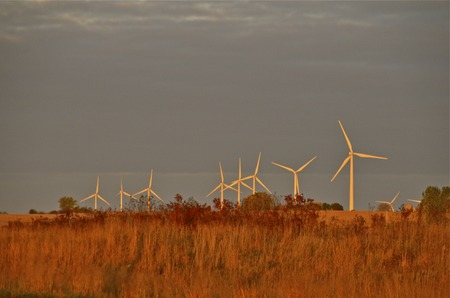 glisten: The blades wind turbine glisten in the early morning sunlight against the autumn colors. Stock Photo