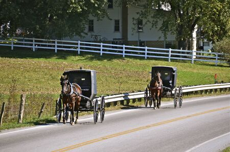 Two Amish buggies travel on a public highway Stock Photo