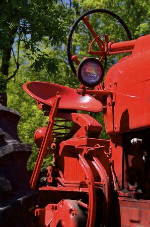 refurbished: Bright red refurbished tractor displays the seat and steering wheel Stock Photo