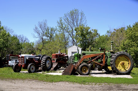 old tractors: A cluster of colorful old tractors are parked on a concrete slab Stock Photo