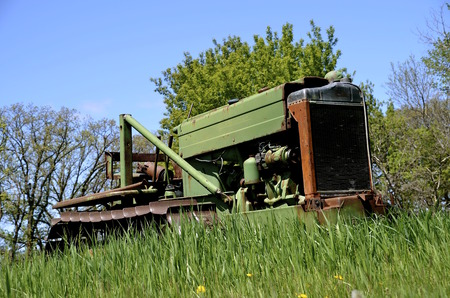 long  ago: An old bulldozer from years ago is retired and parked in the long grass Stock Photo