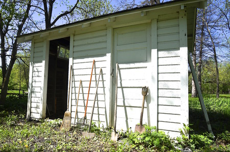An old garden shed with a door open and a door closed has tools leaning against the siding. Фото со стока