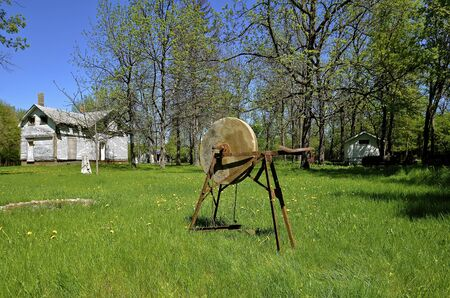 homestead: An old antique grindstone is placed in the yard of a rural homestead which is abandoned.