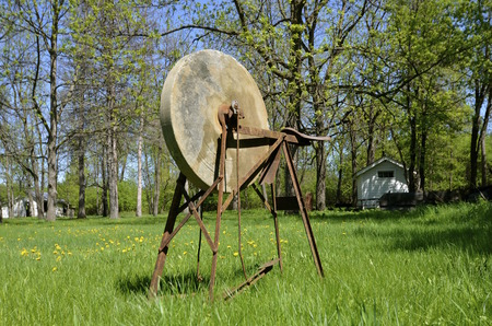 farmstead: An old grindstone is located in the yard of abandoned farmstead. Stock Photo