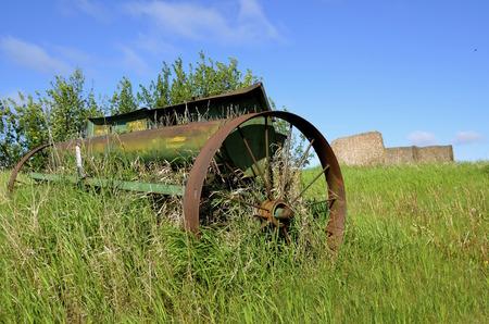 駐車農村フィールドで干し草の俵をバック グラウンドで古い穀物種をまくには、開いたままシード ボックス蓋があります。