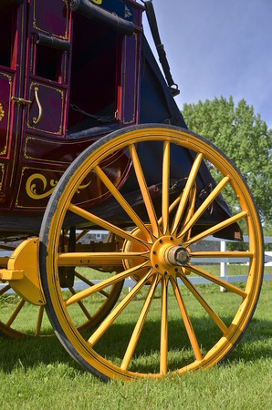 usps: A beautiful yellow painted wooden wheel of a stagecoach glistens in the sun.