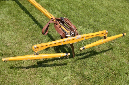hitch: A double tree hitch is brightly painted yellow and ready to be hooked up to several horses