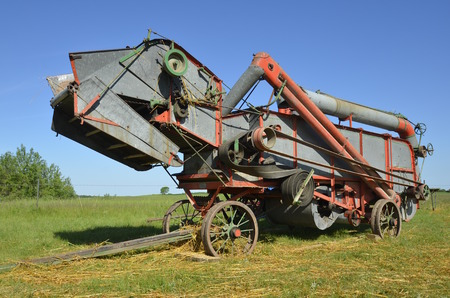 thresh: An old antique threshing machine is in working condition and has scattered straw around the base of the machine. Stock Photo