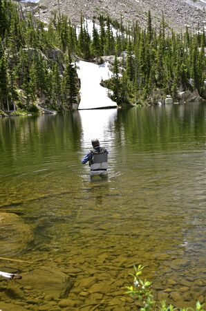 waders: A fly fisherman is in waders on a lake with surrounded by glaciers at Rocky Mountain National Park.