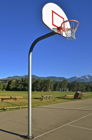 outdoor basketball court: Outdoor basketball court with hoop, rim, net, and backboard against a backdrop of the Rocky Mountains